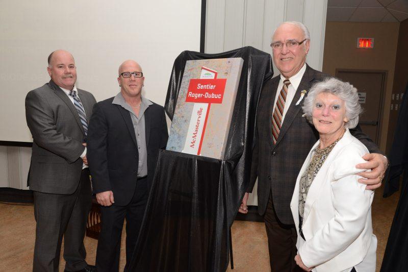 Le maire de McMasterville Gilles Plante présente la plaque honorifique aux membres de la famille Dubuc.