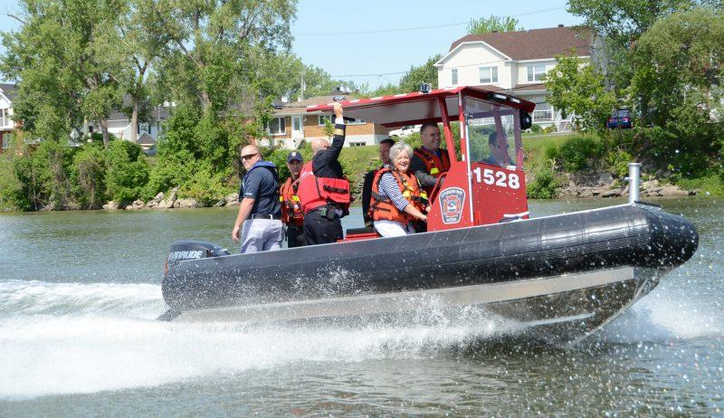 La mairesse Danielle Lavoie en compagnie des pompiers des membres du service sécurité incendie sur la nouvelle embarcation du service.