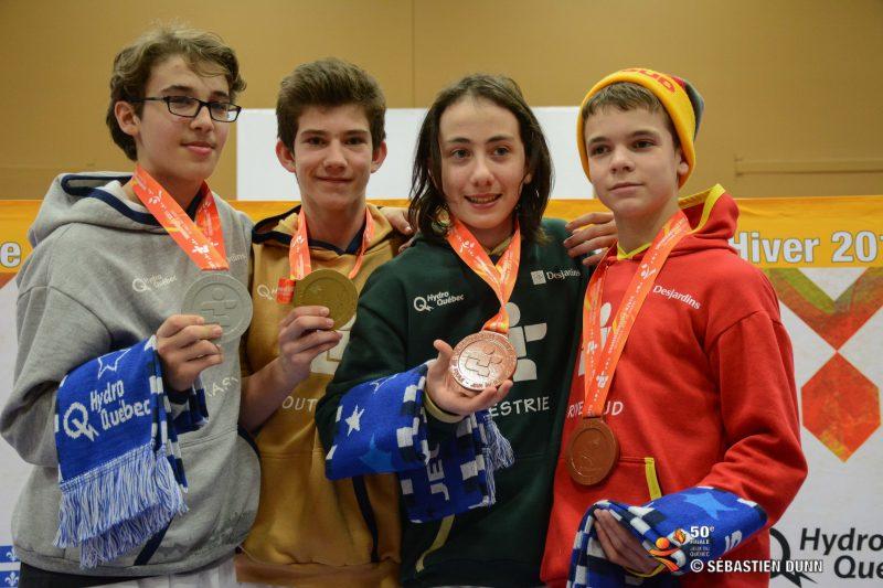 Mathieu Bissonnette (à droite en rouge) tenant sa médaille de bronze obtenue aux Jeux du Québec en combat individuel.