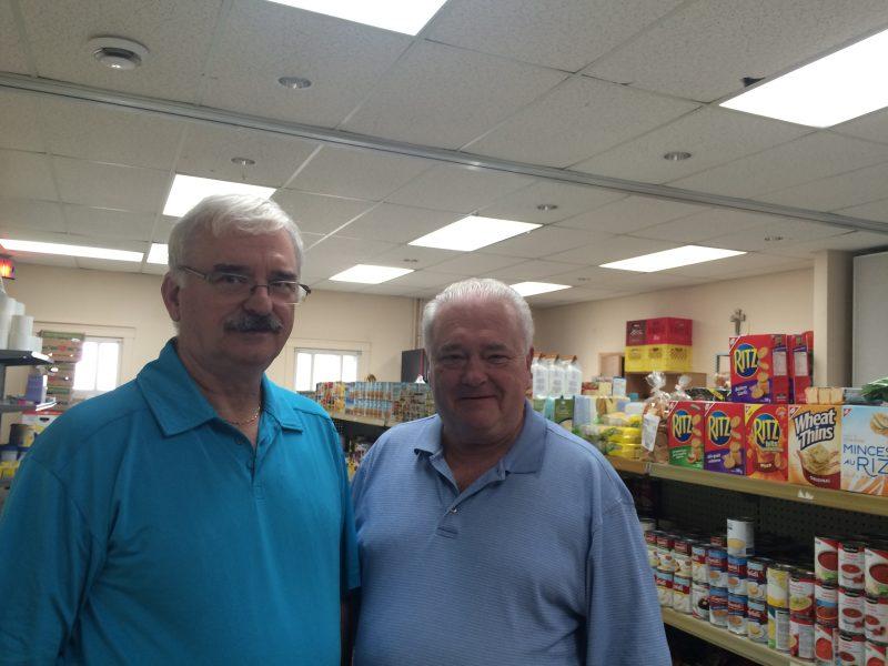 Sylvio Bienvenue et Claude Lebrun devant le nouveau local du comptoir alimentaire.