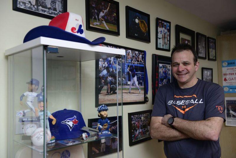 André Bergeron posant fièrement devant une partie de sa collection d'objets de baseball.