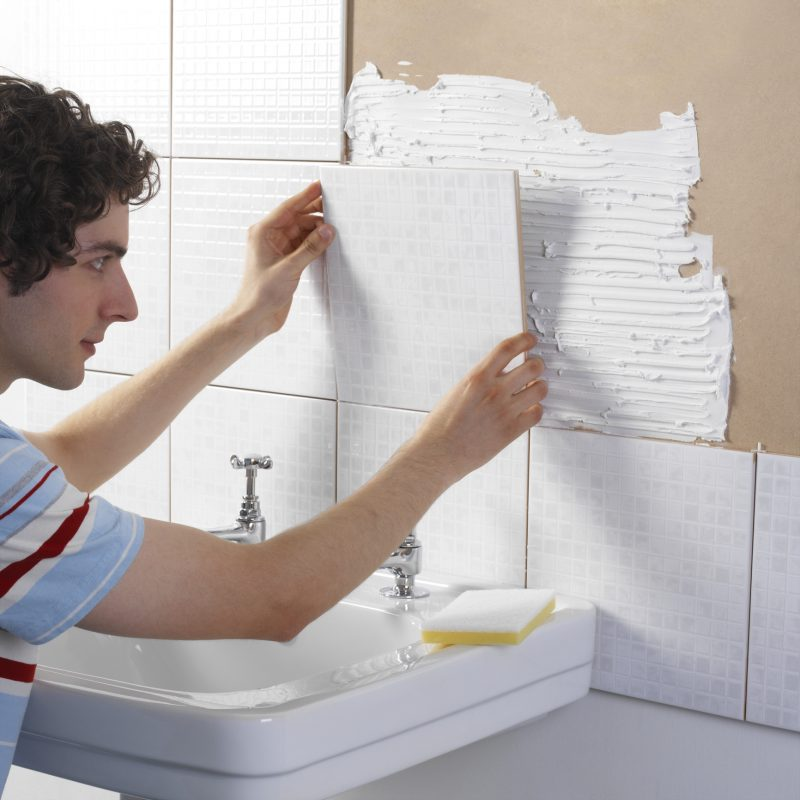 Man re-tiling bathroom wall