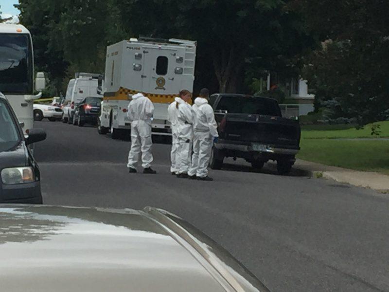 Les enquêteurs de la division de l'identité judiciaire de la SQ, vêtus d'une combinaison blanche, passent au peigne fin la maison afin de trouver des indices permettant de localiser Cheryl Bau Tremblay.