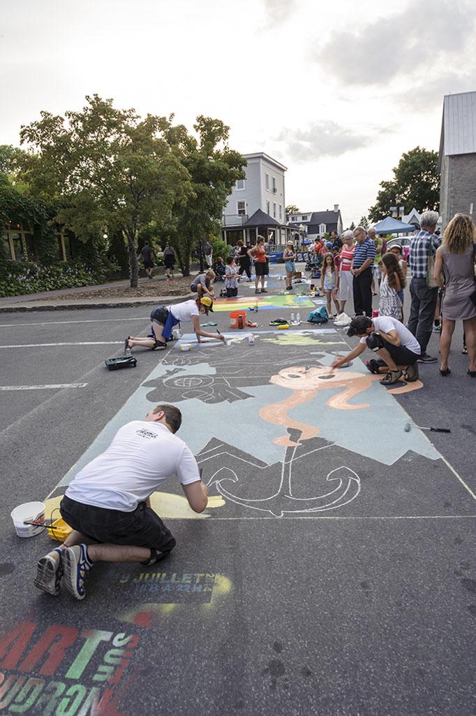 Un artiste peint en direct dans les rues du Vieux-Beloeil à l'occasion de l'événement L'art sur Goudron.