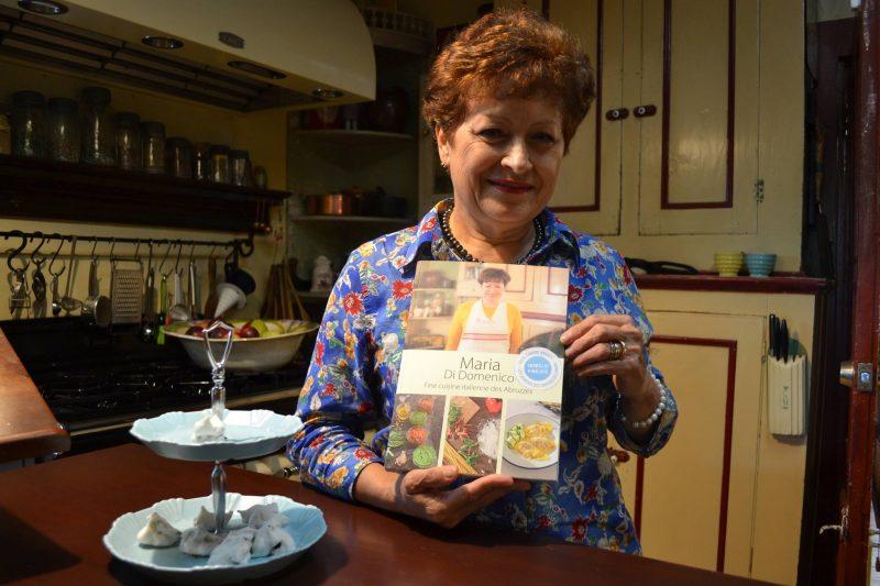 Maria Di Domenico tient son premier livre dans le confort de sa cuisine, aussi sa salle de cours.