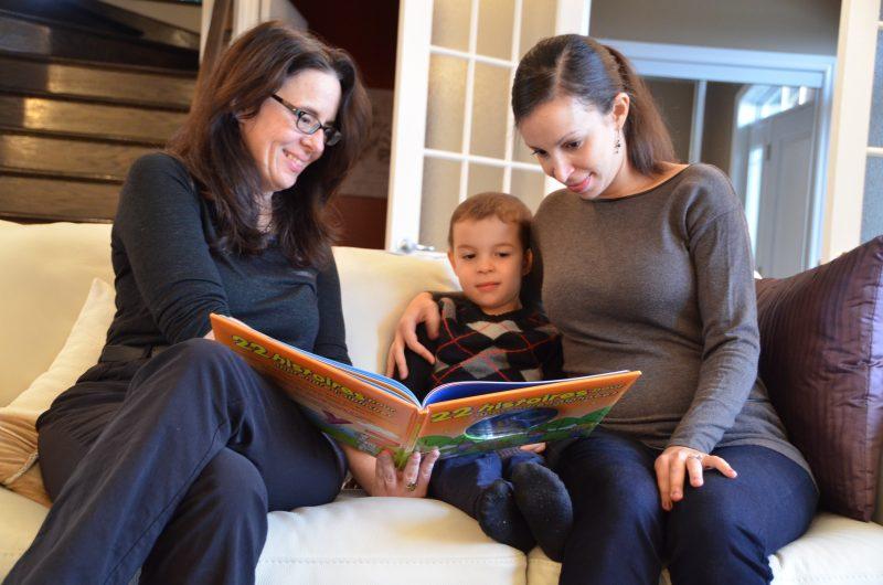 La bibliothécaire Sophie Morissette, Charles Lafrance et sa mère Zahra Bouna Aly partagent un bon moment devant l'un des nombreux livres de l'enfant.