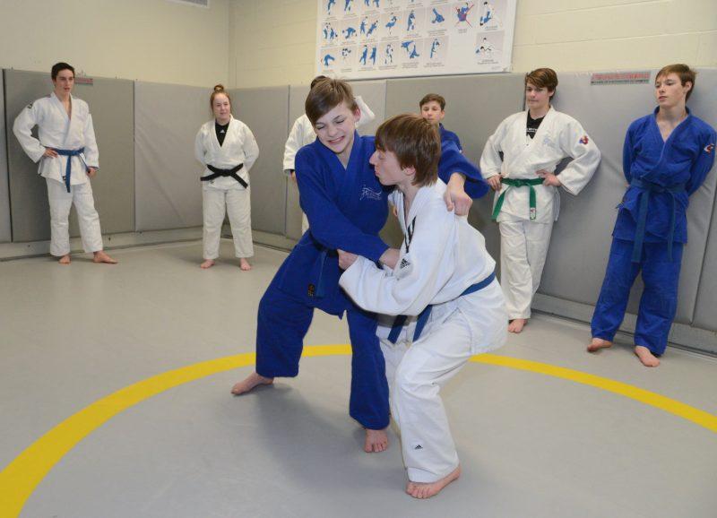 Audrey Dion (2e en arrière à gauche) observant ses judokas sur le tatami.
