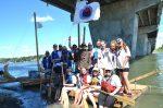 Des scouts descendent la rivière en radeau de fortune