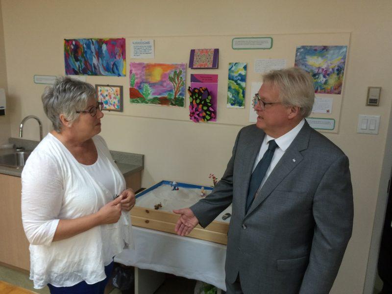 Le ministre Gaétan Barrette regarde les résultats de la salle d'expression par l'art lors de l'inauguration du centre de jour de la maison Victor-Gadbois.