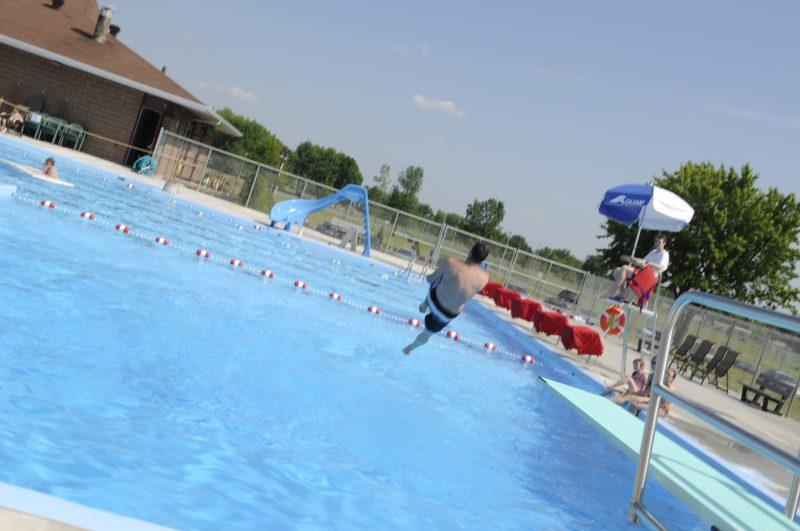 Un enfant saute à l'eau dans une pisicne municipale.