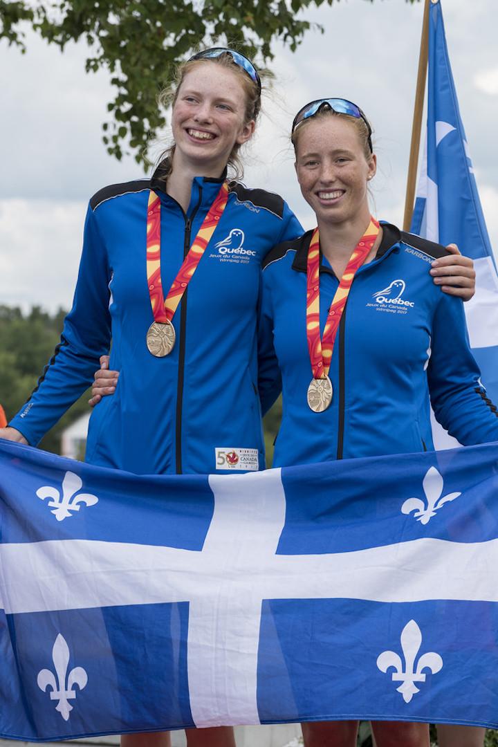 Marilou Duvernay-Tardif (gauche) brandissant fièrement le drapeau du Québec avec la médaille d'or au cou. Photo: Jeux du Canada