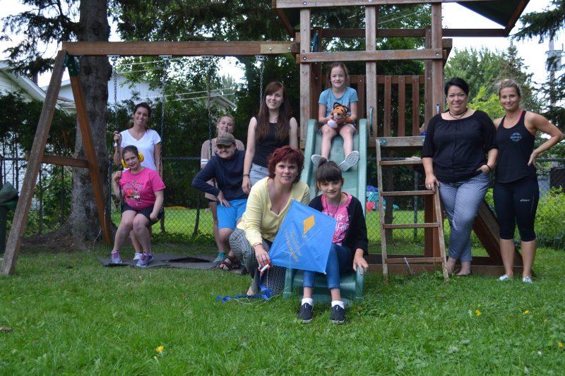 Marie Houle, Martine Riopelle, les éducatrices et les enfants dans la cour extérieure de la Maison de répit. Photo: Karine Guillet