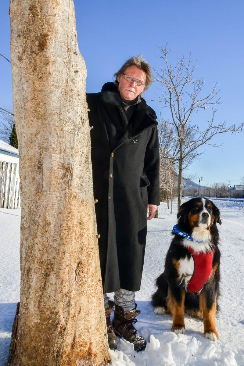 Daniel-Vincent Bernard, en compagnie de son chien Amos, à côté d'un des arbres qu'il sculptera très prochainement au bord de la rue Saint-Jean-Baptiste à Belœil. Photo: François Larivière