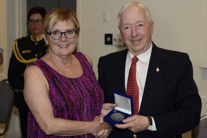 La bénévole Monique Éthier reçoit la médaille du Lieutenant-Gouverneur des mains de l'honorable Michel Doyon.  Photos: Yann Canno