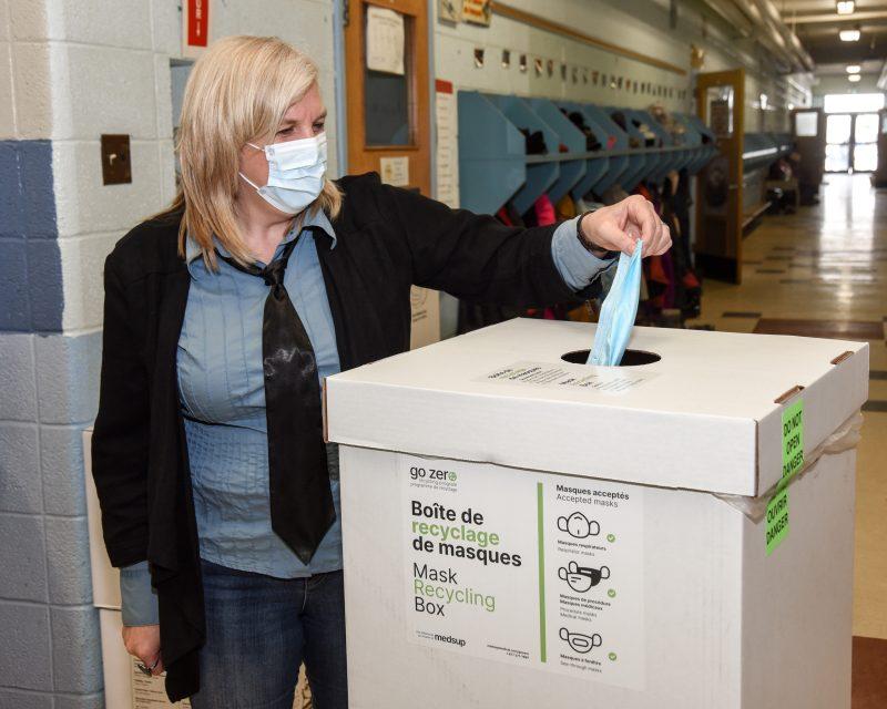 Sophie Lapointe, directrice de l'école Mountainview, dépose un masque de procédure au recyclage. Photo François Larivière | L'Œil Régional ©