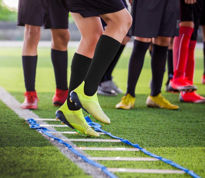 Soccer player Jogging and jump between marker for football training. Ladder Drills Exercises for Football Soccer team. Young player exercises on ladder drills.